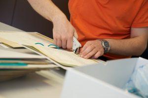 Auszubildender beim Entfernen von Heftklammern